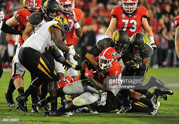 Charles Harris and Marcell Frazier of the Missouri Tigers strip the ball away from Sony Michel of the Georgia Bulldogs on October 17 2015 in Atlanta...