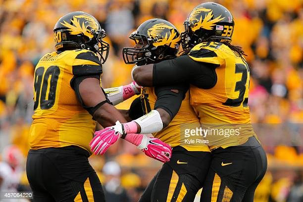 Charles Harris is embraced by Harold Brantley and Markus Golden of the Missouri Tigers after Charles Harris completed on a sack on third down against...
