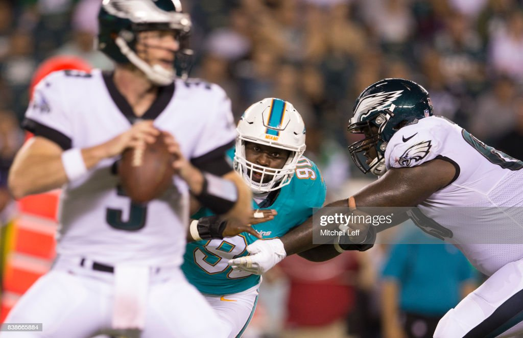 Charles Harris #90 of the Miami Dolphins rushes after Matt McGloin #3 of the Philadelphia Eagles with Dillon Gordon #69 of the Philadelphia Eagles guarding him in the fourth quarter of the preseason game at Lincoln Financial Field on August 24, 2017 in Philadelphia, Pennsylvania. The Eagles defeated the Dolphins 38-31.