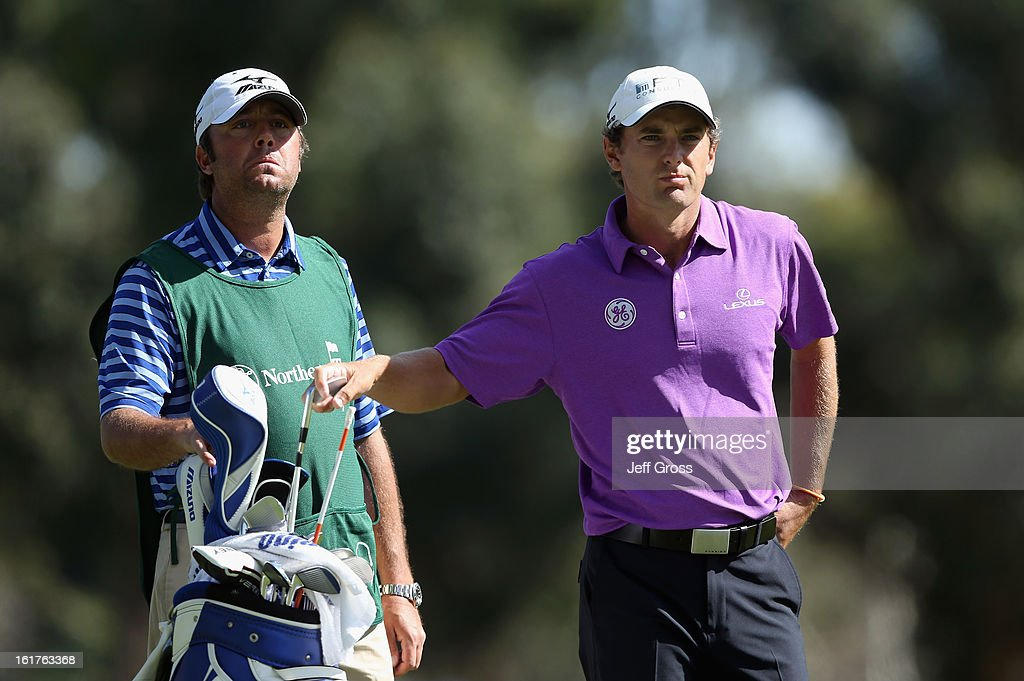 Charles Howell III (R) pulls a club from the bag, as his caddie Henry Diana looks on during the second round of the Northern Trust Open at Riviera Country Club on February 15, 2013 in Pacific Palisades, California.