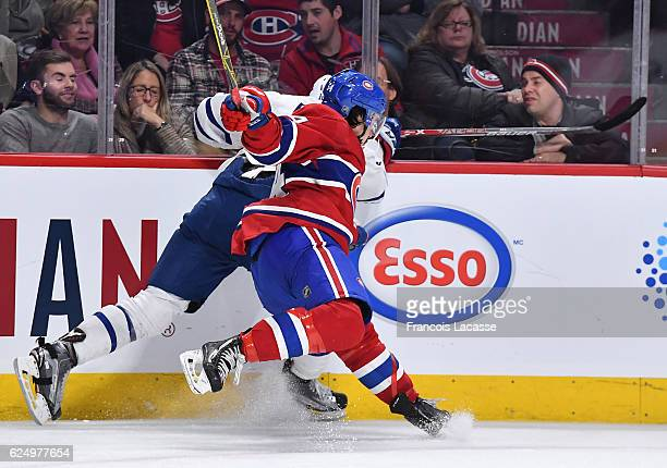 Charles Hudon of the Montreal Canadiens checks into the boards Connor Brown of the Toronto Maple Leafs in the NHL game at the Bell Centre on November...