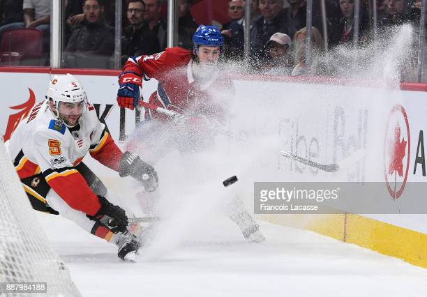 Charles Hudon of the Montreal Canadiens digs the puck out from along the boards under pressure of Mark Giordano of the Calgary Flames in the NHL game...