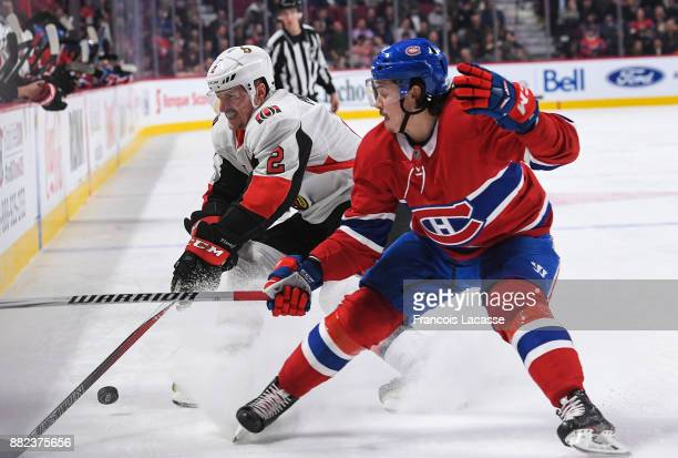 Charles Hudon of the Montreal Canadiens fights for the puck against Dion Phaneuf of the Ottawa Senators in the NHL game at the Bell Centre on...