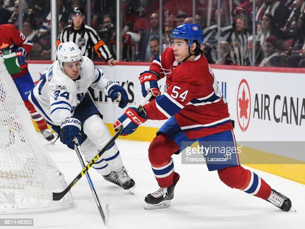 Charles Hudon of the Montreal Canadiens passes the puck against pressure from Auston Matthews of the Toronto Maple Leafs in the NHL game at the Bell...