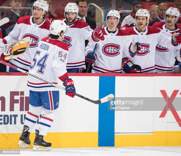 Charles Hudon of the Montreal Canadiens pounds gloves with teammates on the bench following his second period goal during an NHL game against the...