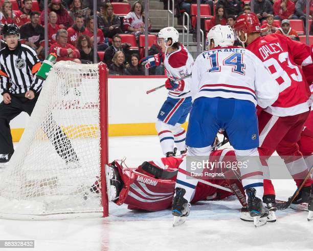 Charles Hudon of the Montreal Canadiens scores a second period goal on Jimmy Howard of the Detroit Red Wings while Trevor Daley of the Wings and...