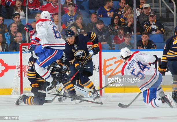 Charles Hudon of the Montreal Canadiens shoots the puck while defended by Matt Tennyson and Robin Lehner of the Buffalo Sabres during an NHL game on...