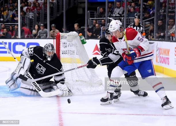 Charles Hudon of the Montreal Canadiens skates after the puck with Alec Martinez of the Los Angeles Kings as Jonathan Quick looks on at Staples...