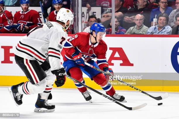 Charles Hudon of the Montreal Canadiens skates the puck against Brent Seabrook of the Chicago Blackhawks during the NHL game at the Bell Centre on...