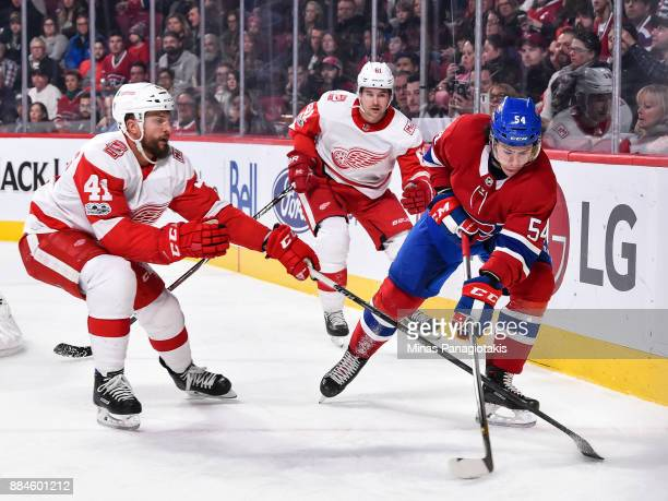 Charles Hudon of the Montreal Canadiens skates the puck against Luke Glendening of the Detroit Red Wings during the NHL game at the Bell Centre on...