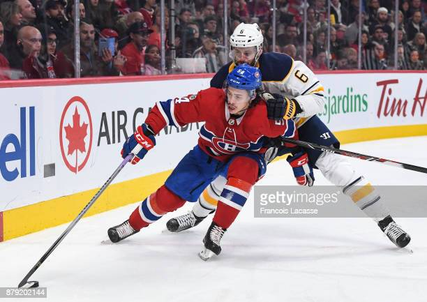 Charles Hudon of the Montreal Canadiens skates with the puck under pressure from Marco Scandella of the Buffalo Sabres in the NHL game at the Bell...