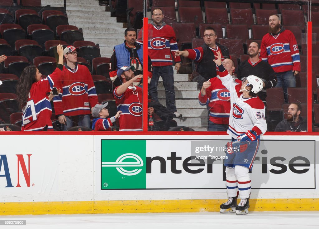 Charles Hudon #54 of the Montreal Canadiens throws a souvenir puck over the glass to fans as he is named the first star of the game after a win against the Ottawa Senators at Canadian Tire Centre on October 30, 2017 in Ottawa, Ontario, Canada.
