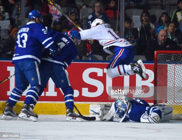 Charles Hudon of the St John's IceCaps leaps over goalie Garret Sparks of the Toronto Marlies while Frederik Gauthier and Justin Holl of the Marlies...