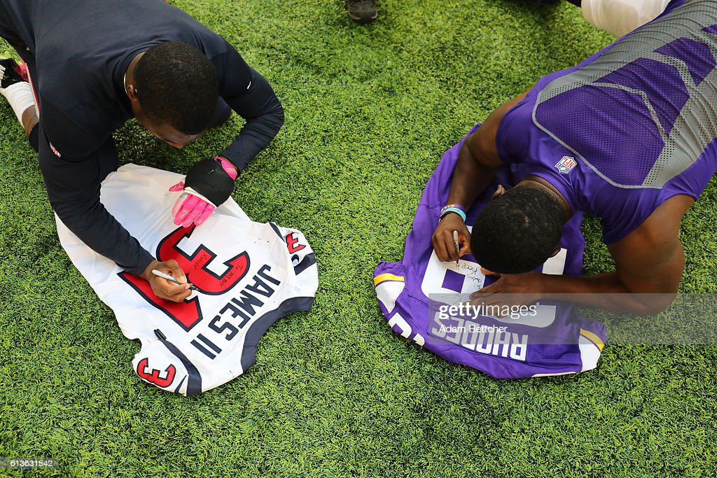 Charles James of the Houston Texans and Xavier Rhodes of the Minnesota Vikings autograph each others jerseys after the game on October 9 2016 at US...