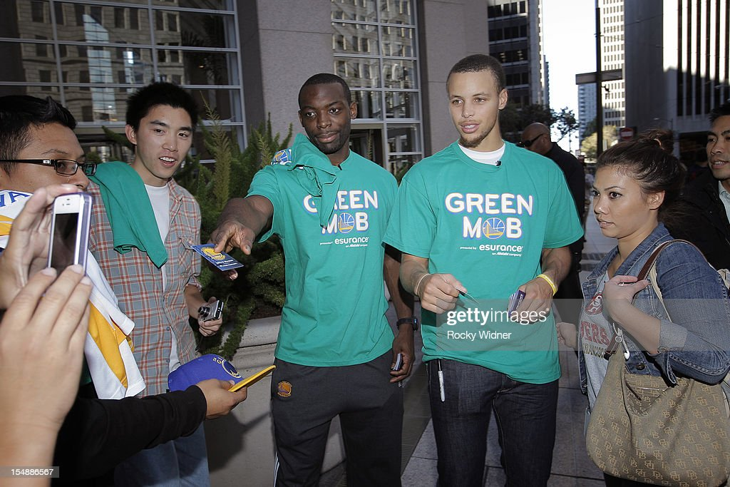 Charles Jenkins and Stephen Curry of the Golden State Warriors hand out free Clipper cards to fans on October 26, 2012 in Oakland, California.