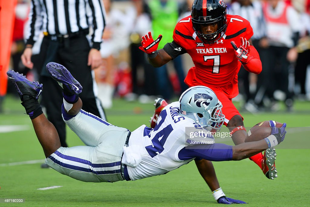 Charles Jones of the Kansas State Wildcats reaches for the end zone against the defense of Jah'Shawn Johnson of the Texas Tech Red Raiders during the...
