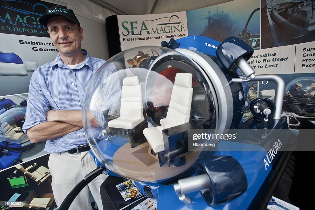 Charles Kohnen, co-founder of SEAmagine Hydrospace Corp. poses for a photograph beside a model of an AURORA 3 person submarine vessel during the Monaco Yacht Show (MYS) in Monaco, France, on Thursday, Sept. 26, 2013. Over 100 of the world's luxury yachts will be displayed in Port Hercules during the 23rd MYS which runs from Sept. 25 - 28. Photographer: Balint Porneczi/Bloomberg via Getty Images