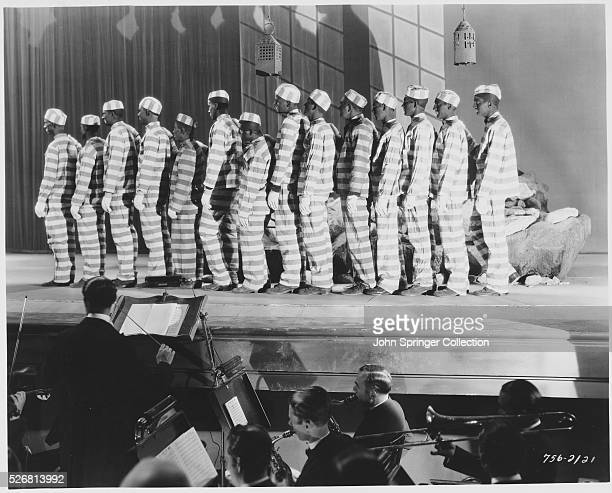 Charles Mack and George Moran dressed as convicts and in blackface join the line of prisoners on stage