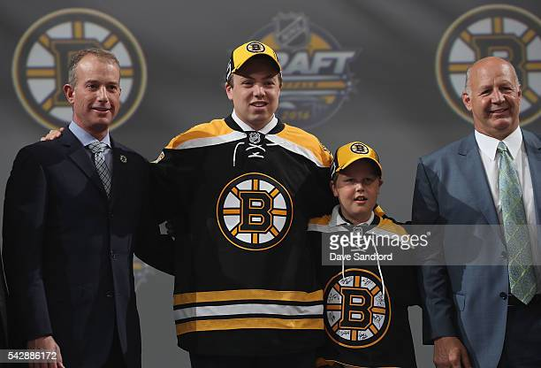 Charles McAvoy stands with Chief Executive Officer Charlie Jacobs and head coach Claude Julien after being selected 14th overall by the Boston Bruins...