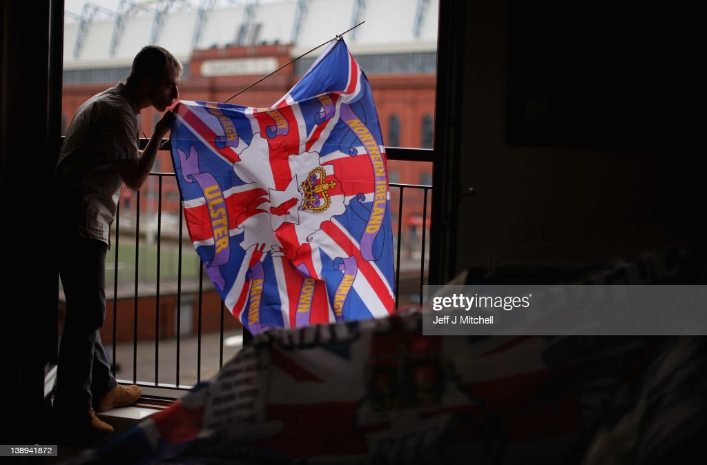 Charles McDonald holds flags outside the window of his home opposite Ibrox Stadium on February 14, 2012 in Glasgow, Scotland. HM Revenue and Customs are in the process of asking the Court of Session to put Glasgow Rangers Football Club into administration. This counteracts moves by owner Craig Whyte, who yesterday gave notice of the clubs intent to go into administration. HMRC is in dispute with the Scottish Premier League Champions over a £49million pound tax bill.
