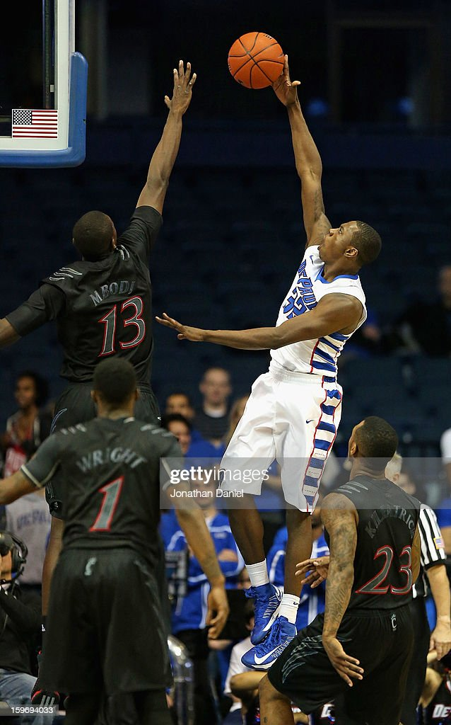 Charles McKinney #32 of the DePaul Blue Demons puts up a shot over Cheikh Mbodj #13, Cashmere Wright #1 and Sean Kilpatrick #23 of the Cincinnati Bearcats at Allstate Arena on January 15, 2013 in Rosemont, Illinois. Cincinnati defeated DePaul 75-70.