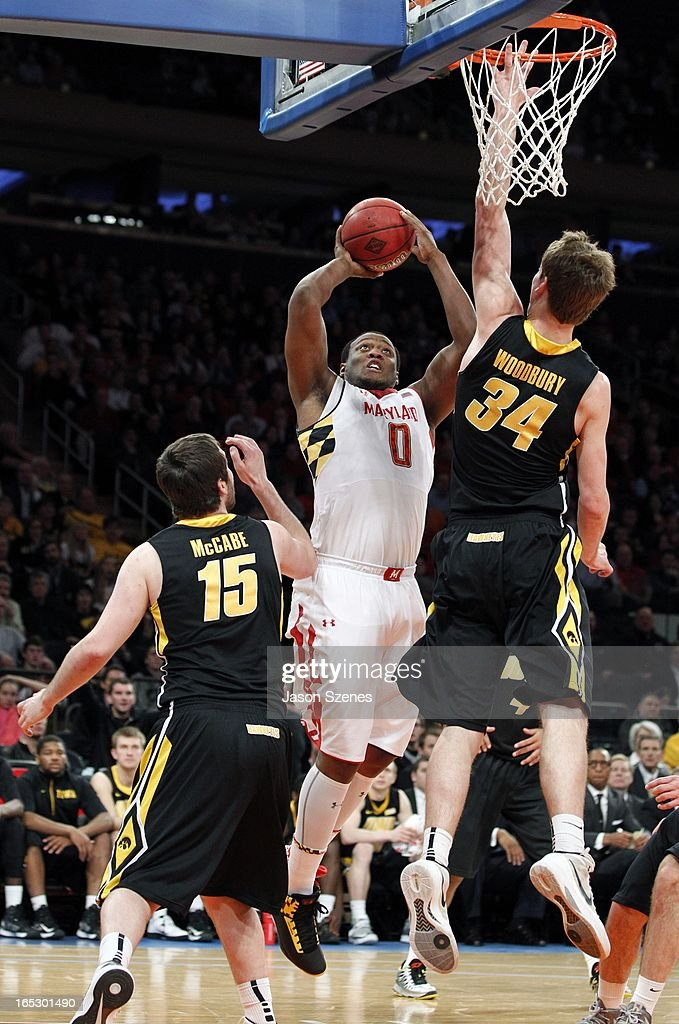 Charles Mitchell #0 of the Maryland Terapins puts up a shot past Zach McCabe #15 and teammate Adam Woodbury #34 of the Iowa Hawkeyes in the first half during the 2013 NIT Championship - Semifinals at the Madison Square Garden on April 2, 2013 in New York City.