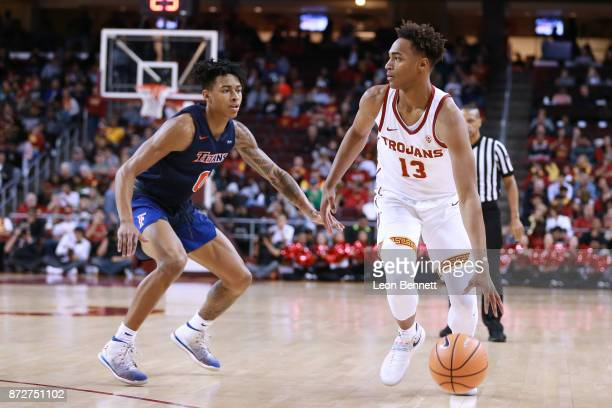 Charles O'Bannon Jr #13 of the USC Trojans handles the ball against Kyle Allman of the CalState Fullerton Titans during a college basketball game at...