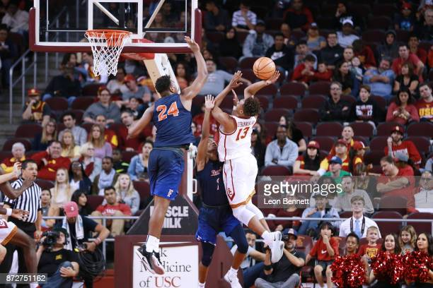 Charles O'Bannon Jr #13 of the USC Trojans handles the ball against Josh Pitts of the CalState Fullerton Titans during a at Galen Center on November...