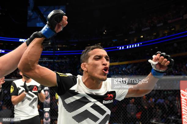 Charles Oliveira of Brazil celebrates his rear choke submission victory against Will Brooks in their lightweight bout during the UFC 210 event at...