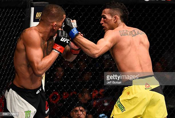 Charles Oliveira of Brazil punches Anthony Pettis of the United States in their featherweight bout during the UFC Fight Night event at Rogers Arena...