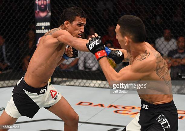 Charles Oliveira of Brazil punches Max Holloway of the United States in their featherweight bout during the UFC event at the SaskTel Centre on August...