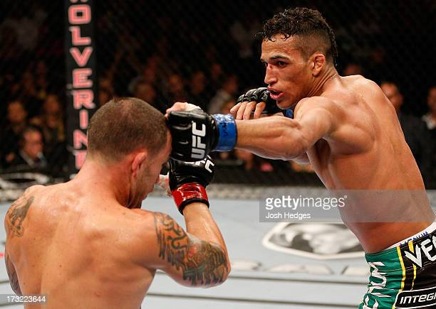 Charles Oliveira punches Frankie Edgar in their featherweight fight during the UFC 162 event inside the MGM Grand Garden Arena on July 6 2013 in Las...