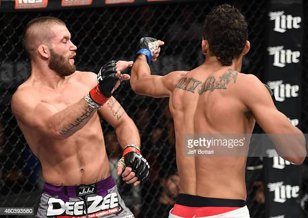 Charles Oliveira punches Jeremy Stephens in their lightweight fight during The Ultimate Fighter Finale event inside the Pearl concert theater at the...