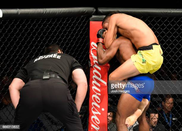 Charles Oliveira secures a rear choke submission victory against Will Brooks in their lightweight bout during the UFC 210 event at KeyBank Center on...