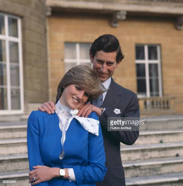 Charles Prince of Wales laughing with his fiancee Lady Diana Spencer outside Buckingham Palace London after announcing their engagement