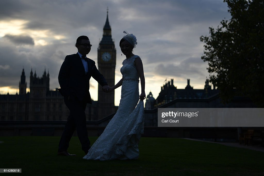 Charles Qian and his fiance Echo Li pose during a pre-wedding photography shoot opposite the Palace of Westminster on October 11, 2016 in London, England. It's a Chinese custom for couples to have their wedding photos taken before they are married and on the wedding day the photos will be shown to guests on cards and big screens. Photography studios such as J.R Studios in east London have seen business boom as the capital has become increasingly popular as a location for pre-wedding photography thanks in part to its instantly recognisable landmarks.