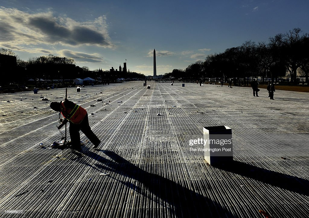 Charles Smith, who works for the Dept. of the Interior, had to remove by hand the sticks that earlier had flags attached to them. They had to be broken up in order to go in the plastic bags as he and a crew worked to clean the mall. Crowds on the National Mall during Inauguration events today. Photo by Michael S. Williamson/The Washington Post via Getty Images
