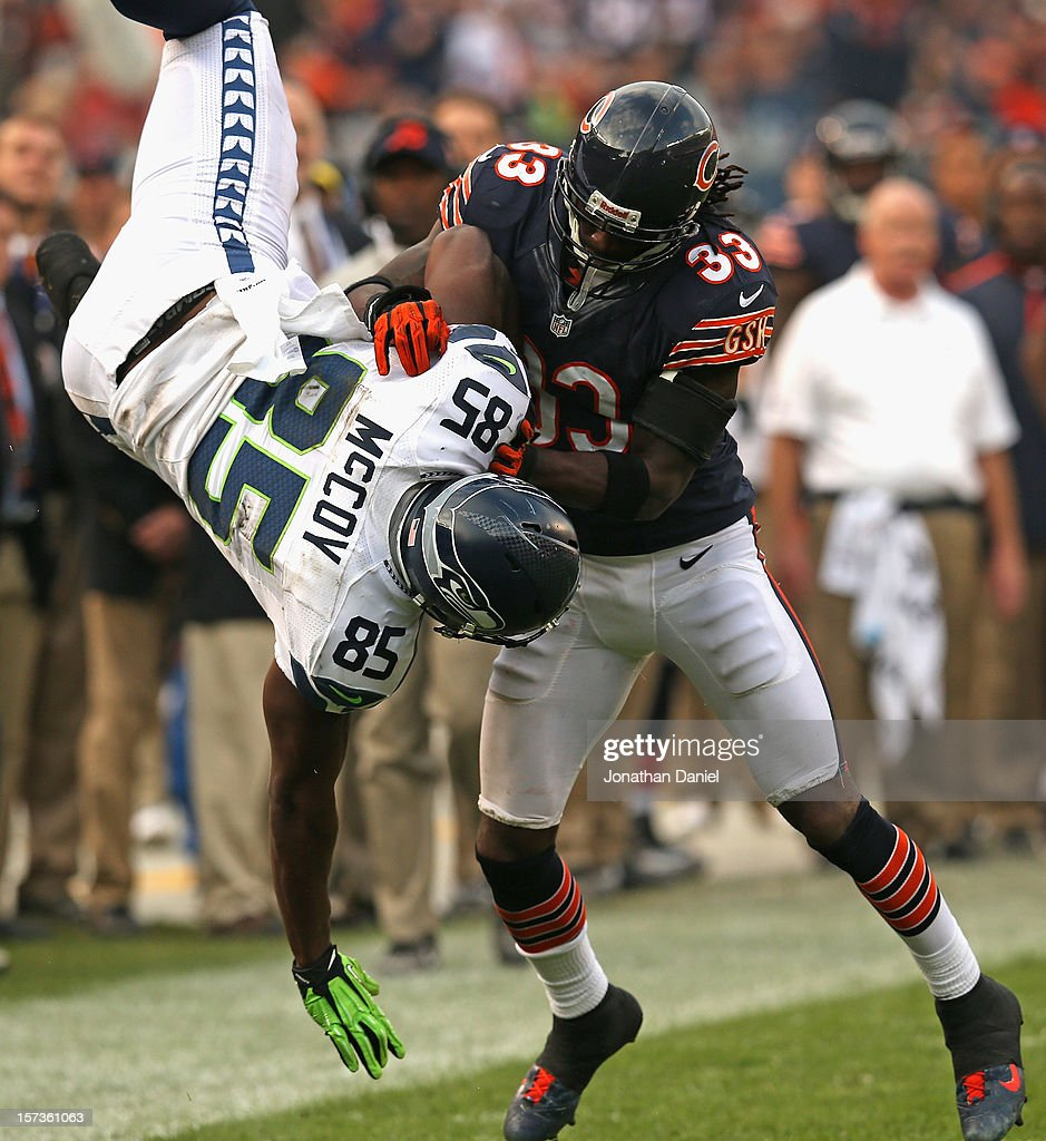 Charles Tillman #33 of the Chicago Bears upends Anthony McCoy #85 of the Seattle Seahawks at Soldier Field on December 2, 2012 in Chicago, Illinois. The Seahawks defeated the Bears 23-17 in overtime.