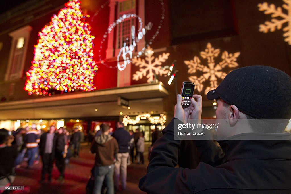 Charles Underwood of Boston takes a picture of the 60-foot-tall tree from Groton, Mass. which is adorned with 10,000 multi-colored lights in front of Macy's Downtown Crossing after the Christmas Tree Lighting Ceremony on Friday, Nov. 25, 2011.