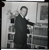 Charles Van Doren noted quiz show whiz for the 'TentyOne' show is shown standing near a bookstand November 21 1959