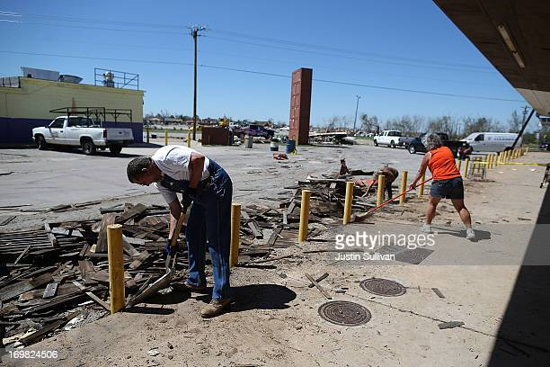 Charles Walker and Gail Middleton clean up debris from in front of a strip mall that was damaged by a tornado on June 2 2013 in Moore Oklahoma...