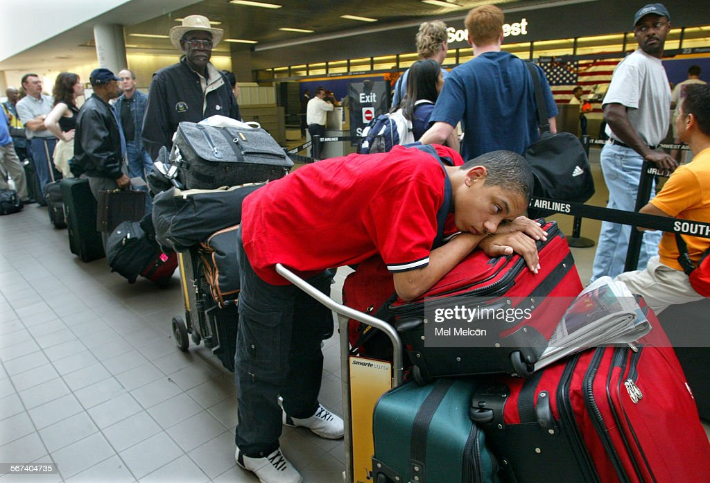 Charles White of Sacramento waits in long line on Sunday afternoon at Southwest Airlines terminal at LAX with his grandfather Willie Simmons left...