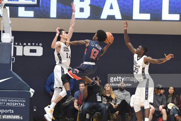 Charles Williams of the Howard Bison drives to the basket between Yuta Watanabe and Bo Ziegler of the George Washington Colonials during a college...
