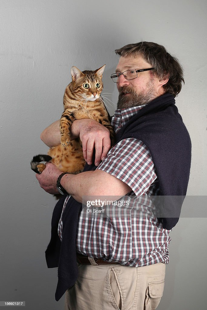 Charles Wilson poses for a photograph with his Brown Spotted Bengal cat named 'Lacemoat-Rocknrola' after being exhibited at the Governing Council of the Cat Fancy's 'Supreme Championship Cat Show' held in the NEC on November 24, 2012 in Birmingham, England. The one-day Supreme Cat Show is one of the largest cat fancy competitions in Europe with over one thousand cats being exhibited. Exhibitors aim to have their cat named as the show's 'Supreme Exhibit' from the winners of the individual categories of: Persian, Semi-Longhair, British, Foreign, Burmese, Oriental, Siamese.