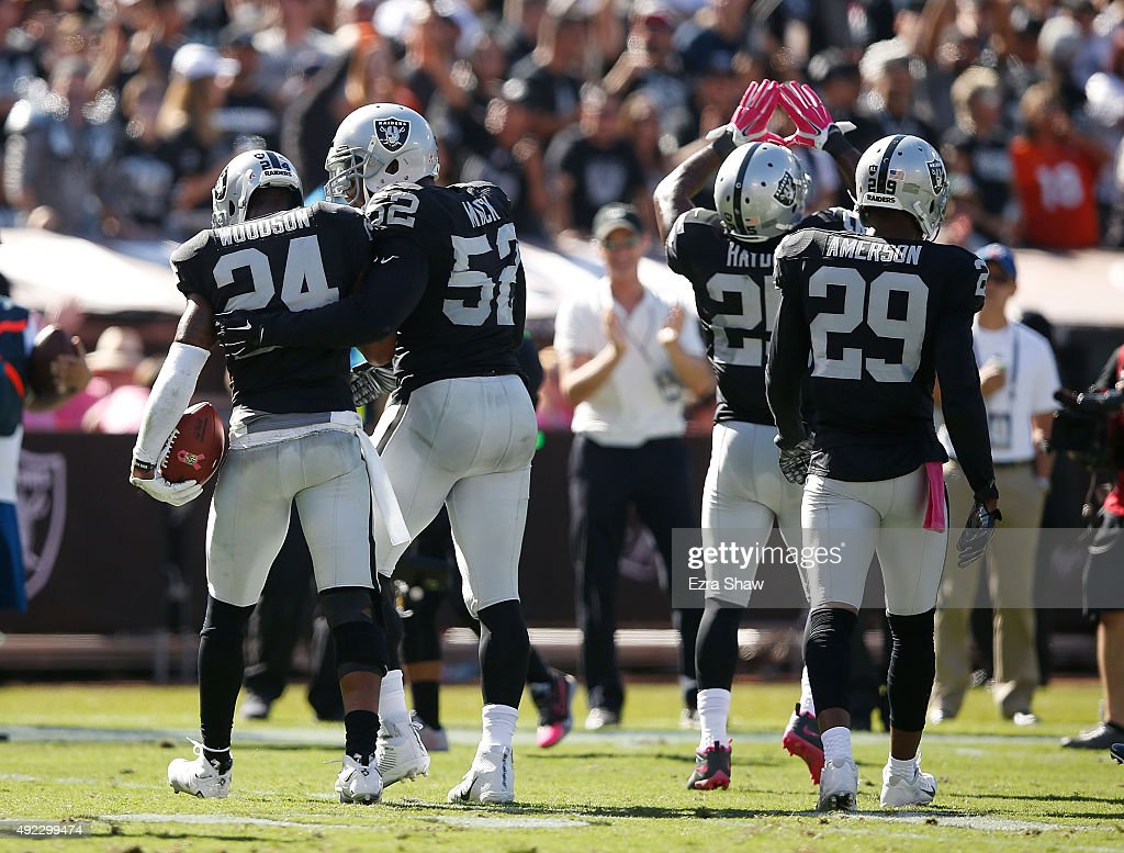 Charles Woodson of the Oakland Raiders celebrates an interception in the second quarter with teammates Khalil Mack of the Oakland Raiders DJ Hayden...