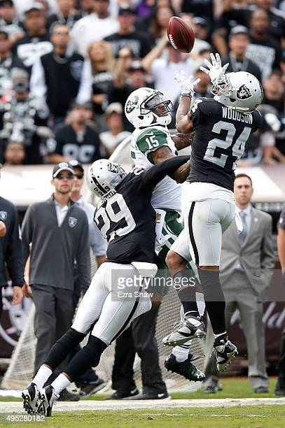 Charles Woodson of the Oakland Raiders intercepts a pass intended for Brandon Marshall of the New York Jets during their NFL game at Oco Coliseum on...