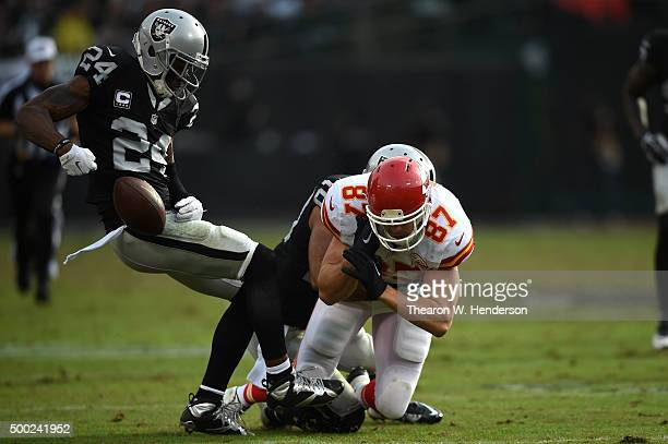 Charles Woodson of the Oakland Raiders strips the ball from Travis Kelce of the Kansas City Chiefs during their NFL game at Oco Coliseum on December...