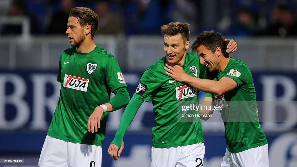 Charles-Elie Laprevotte of Muenster (C) celebrates his team's second goal with his team mates Marcel Reichwein (L) and Stephane Tritz (R) during the Third League match between Wehen Wiesbaden and Preussen Muenster at BRITA-Arena on April 29, 2016 in Wiesbaden, Hesse.