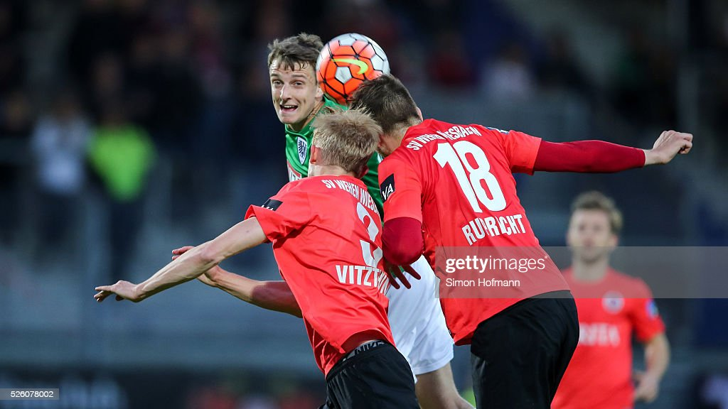 Charles-Elie Laprevotte of Muenster jumps for a header with Steven Ruprecht and Michael Vitzthum (L) of Wiesbaden during the Third League match between Wehen Wiesbaden and Preussen Muenster at BRITA-Arena on April 29, 2016 in Wiesbaden, Hesse.