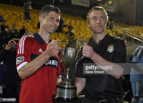 Charleston Battery president Andrew Bell presents team captain Logan Pause of the Chicago Fire with the Carolina Challenge Cup after a game against...